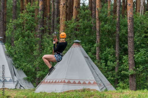 Foto Girl pulls out on a bungee against the background of the forest