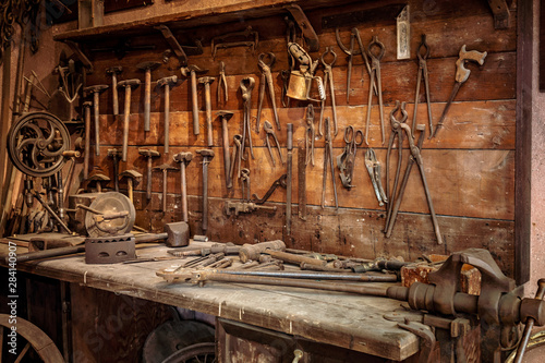 Obraz Complete workbench with a wall of tools in a workshop. Vintage look - fototapety do salonu