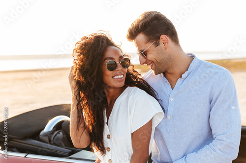 Stampa su Tela  Photo of beautiful multiethnic couple hugging and smiling together while standin