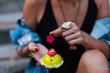 Fashionable woman eating cupcake outdoors