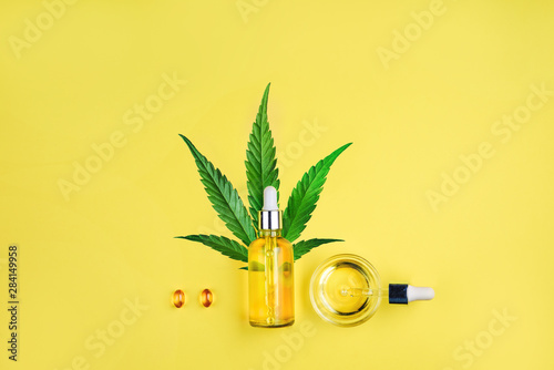 Fototapeta Bottle with CBD oil, pipette, capsules and cannabis leaf on a yellow background. Minimalism, flat lay. obraz