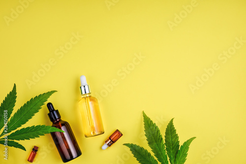 Valokuva  Bottles with CBD oil, a dropper, and leaf marijuana on yellow background