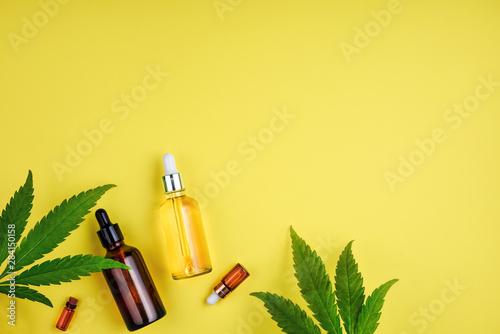 Carta da parati  Bottles with CBD oil, a dropper, and leaf marijuana on yellow background