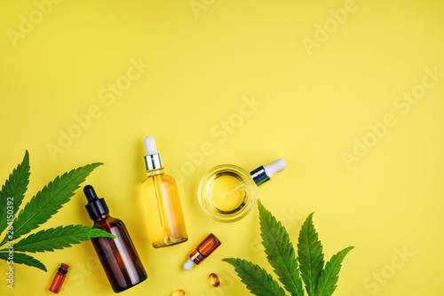 Fotografía  Bottles with CBD oil, a dropper, and leaf cannabis on a yellow background