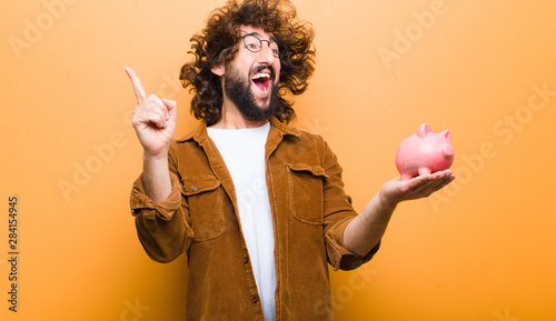 Fotomural young man with crazy hair in motion and a piggy bank