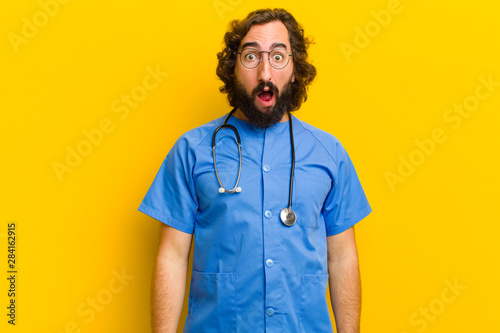 Stampa su Tela  young nurse man surprised or shocked gesture