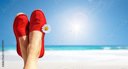 Beine mit roten Stoffschuhen vor Strand und Meer