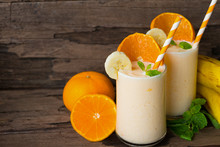 Orange And Banana Smoothies Orange Colorful Fruit Juice Beverage Healthy High Protein The Taste Yummy In Glass On Wood Background.