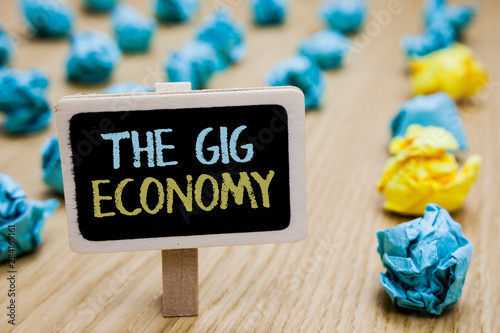 Conceptual hand writing showing The Gig Economy. Business photo text Market of Short-term contracts freelance work temporary poster board with blurry paper lobs laid serially mid yellow lob - 284169161