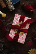 Gift Wrapped With Old-fashioned Patterned Paper And Thick Red Velvet Ribbon Plus Golden Ornaments