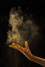 Woman's Hand Scatters Gold Dust On A Black Background With Copy Space. Creative Photo For Your Ideas