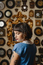 Portrait Of Stylish Tattooed Girl In Front Of The Wall With Clocks