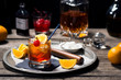 canvas print picture - Old Fashioned Cocktail On Ice with Cherry and Orange Garnish and Ingredients on Bar in Dark Background