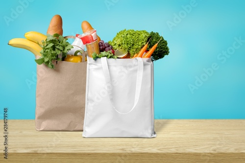 Fotografía  Shopping bags with groceries isolated on white background