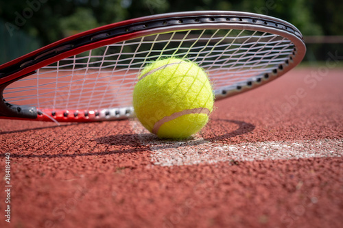 Detail of tennis rocket over ball on court surface