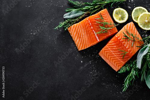 Fototapeta Salmon. Fresh raw salmon fish fillet with cooking ingredients, herbs and lemon on black background, top view obraz