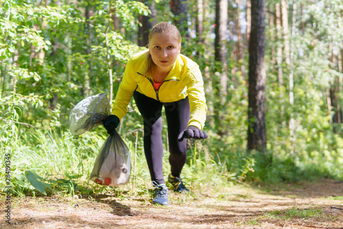 female jogger leans over trash during plogging Tableau sur Toile