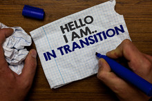 Word Writing Text Hello I Am.. In Transition. Business Concept For Changing Process Progressing Planning New Things Hand Hold Paper Lob And Blue Marker Wooden Base With Torn White Written Page