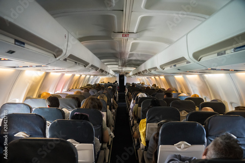 Commercial aircraft cabin with rows of seats down the aisle Wallpaper Mural