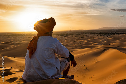 Fotografiet  View from behind of a young native of the desert who observes the dunes in the d