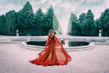 A Mysterious Blond Woman Walks In A Luxurious, Royal Garden. The View From The Back. Princess In A Silk Red Dress With A Long Train. A Feminine Girl Goes With Hope For The Light Of Change To Freedom.
