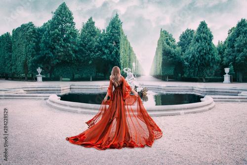 A mysterious blond woman walks in a luxurious, royal garden Fototapete