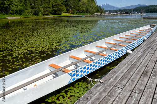 Valokuvatapetti beautiful long wooden white boat at a wooden pier on a picturesque Sproat Lake o
