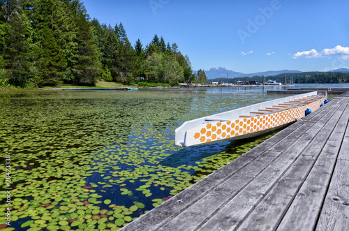 beautiful long wooden white boat at a wooden pier on a picturesque Sproat Lake o Canvas-taulu