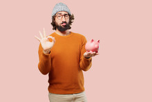Young Bearded Man With A Piggy Bank