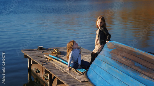 Photo Charming children schoolgirls spending time by lake