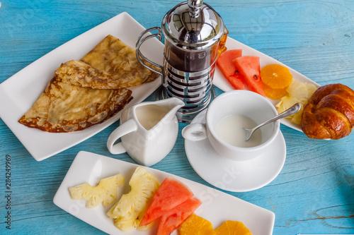 petit-déjeuner avec café, lait, fruits, crêpes et croissant