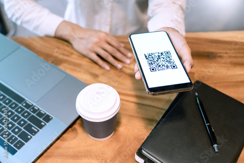 Valokuva  Man's hand holding smartphone with QR code on the screen, payment, E wallet , cashless technology generate digital pay without money