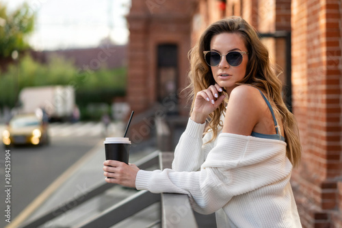 Papiers peints The european girl in white sweater stands on street with paper cup takeaway coffee. Coffee break