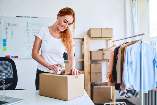 Fototapeta Young small business owner packing deliveries in modern office and storage space obraz