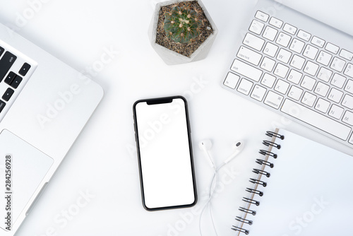 Cuadros en Lienzo Modern white office work table with smartphone mock up laptop ,earphone and catu
