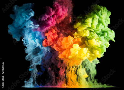 Colorful paint drops from above mixing in water Canvas Print
