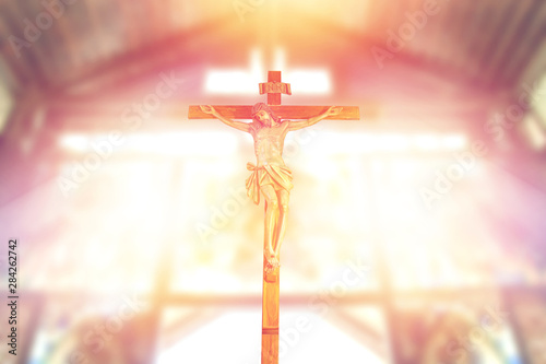Fototapeta  antique wooden crucifix, jesus on the cross in church with ray of light from sta