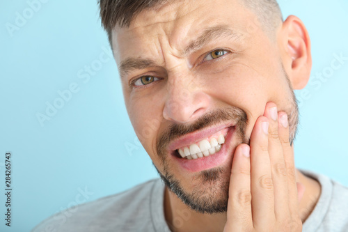 Carta da parati Man suffering from toothache against color background, closeup
