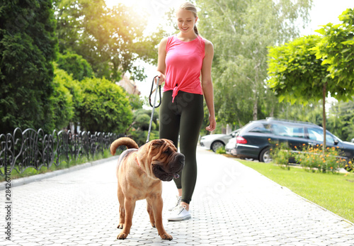 Sporty woman with cute dog walking outdoors Fototapete