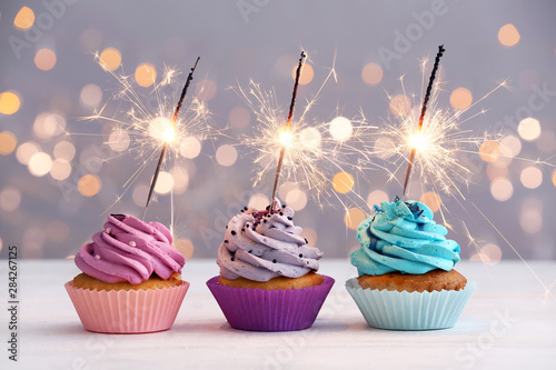 Платно Tasty Birthday cupcakes on table against defocused lights