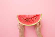 Young Woman Hands Holding Red Piece Of Watermelon On Light Pastel Pink Table. Closeup.