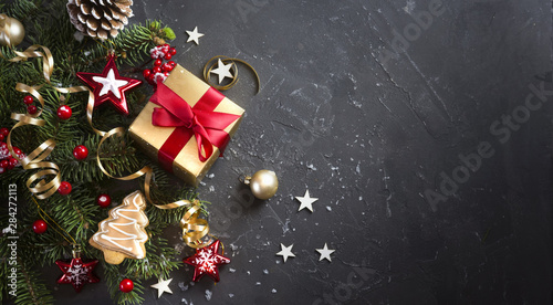 Fotografia Christmas dark black background with beautiful texture and Golden gift box with red ribbon, fir branches, cones, Christmas tree toys stars, Christmas tree cookies, top view, copy space