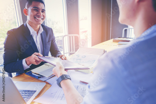 Obraz Businessman exchanging memorandum of understanding with contract papers after agreement. - fototapety do salonu