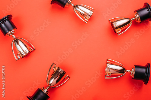 Fototapeta Winner or champion cup on bright background, Flat lay style