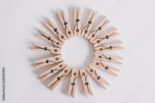 Fototapeta Group of wooden clothespins arranged in a circle isolated on white background