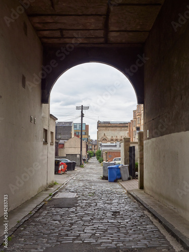 Looking down an Old Passageway with a cobbled road surface on a Cloudy Summers day in Glasgow, Scotland, UK.