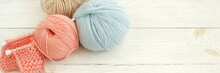Knitting Wool And Knitting Needles In Pastel Blue And Pink Colors On White Wooden Background Banner. Top View.copy Space