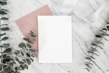 Luxury Wedding Invitation Mock-up Card With Paper And Envelope, Roses, Gifts, Eucalyptus, Ribbon On White Marble Background, Top View, Flat Lay