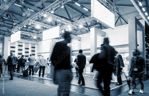 Obraz business people walking at a trade show booth at a public event exhibition hall, with banner and copy space for individual text - fototapety do salonu