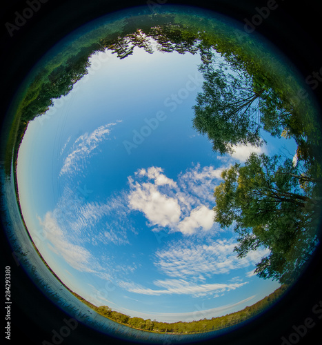 A fisheye view of Russian nature, blue lake and green grass with sunny sky Canvas Print